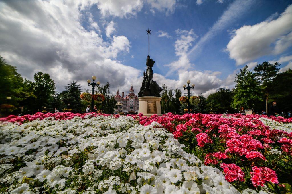 Un parterre de fleur, au centre une sculpture représentant un parchemin et la main de Mickey tenant une baguette magique