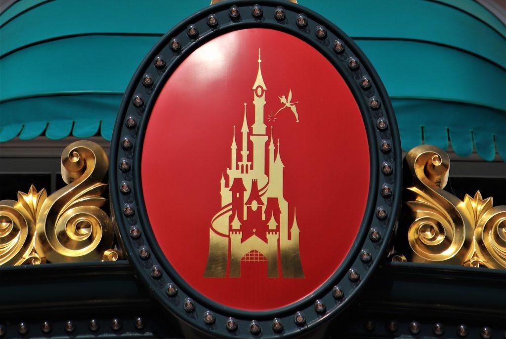 Le logo de disneyland or et rouge, en forme de château, avec la fée clochette