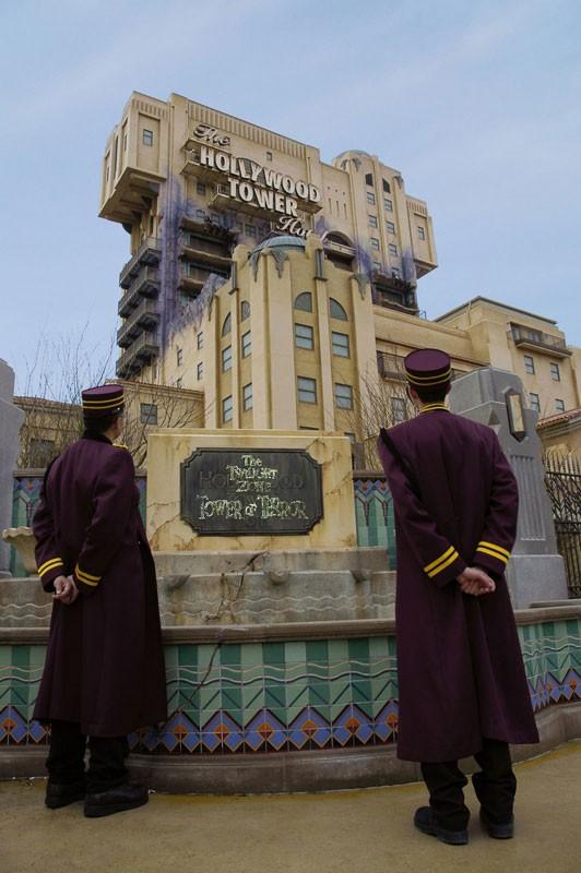 Deux cast members se tiennent devant l'ATTRACTION THE TWILIGHT ZONE TOWER OF teRROR™ à disneyland paris