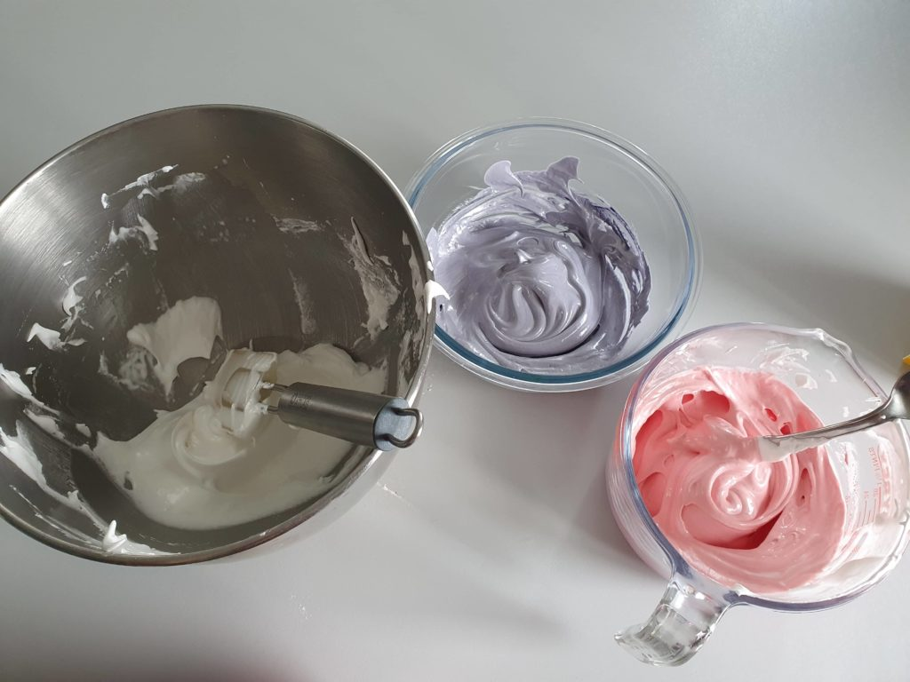 Three containers with different coloured meringue.