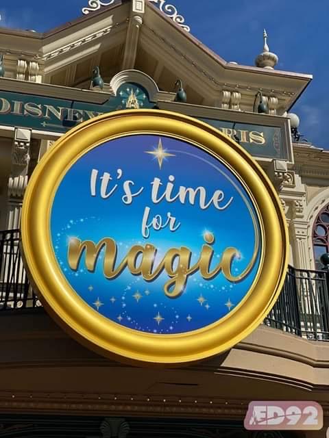 Un panneau lumineux en forme de cercle affiche le slogan It's time for magic, le fond est bleu, le cadre est couleur or