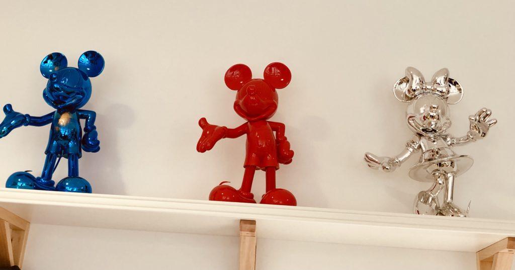 Une sculpture de mickey bleue, une rouge et une de minnie couleur argent.