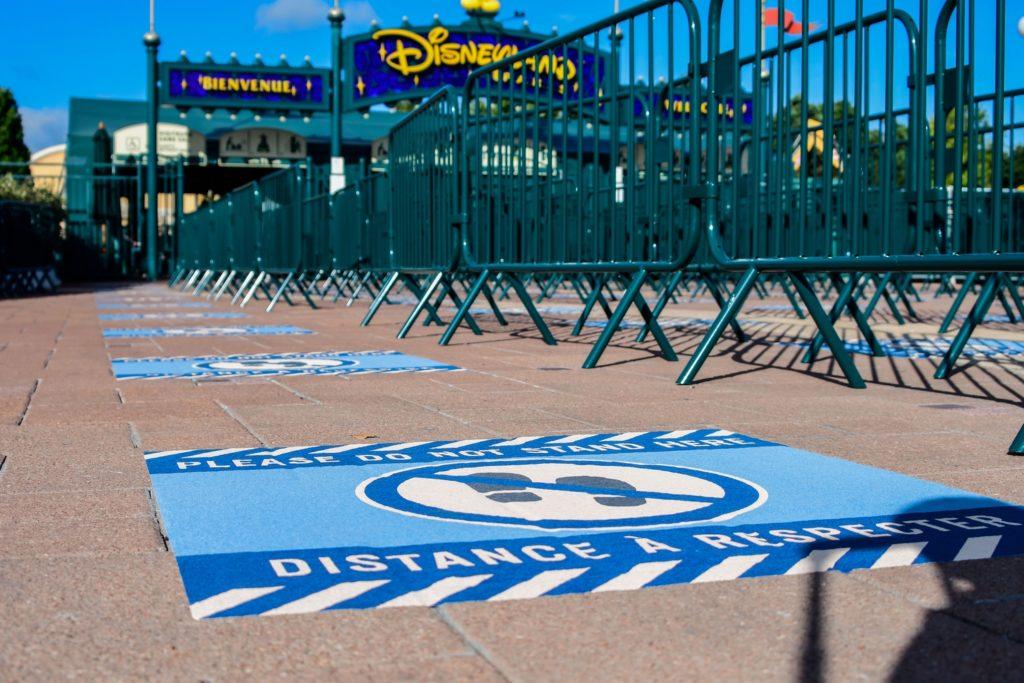 Des barrières vertes canalisent les visiteurs devant l'entrée de Disneyland Paris. Des marquages ont été posés au sol pour respecter les distances de sécurités
