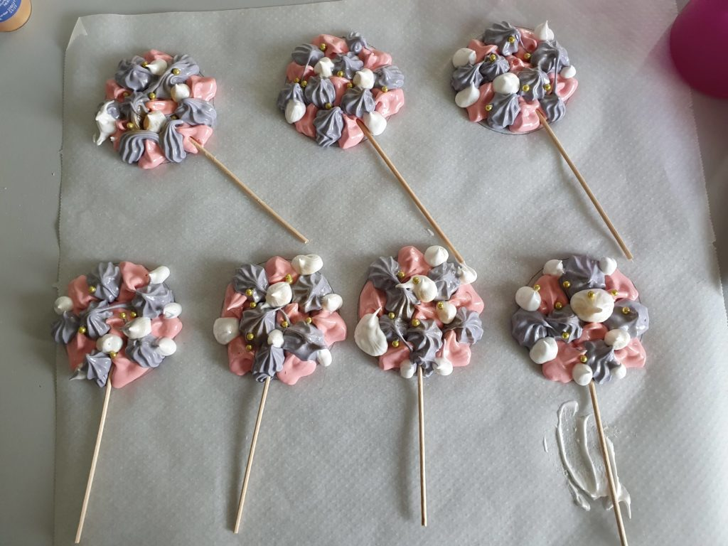 Food pearls and sticks are placed on the meringue to create lollipops