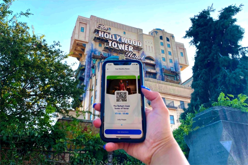 a disney first access on smartphone in front of the tower of terror