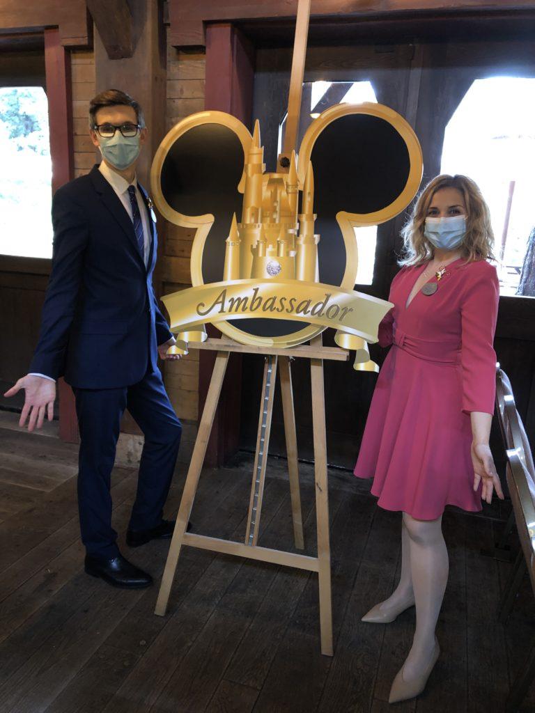 Les deux ambassadeurs de Disneyland Paris prennent la pose devant le logo géant